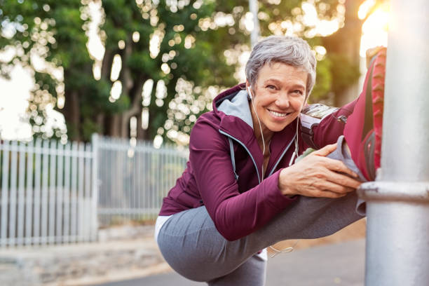 mature woman warming up before jogging - vitality stock photos and pictures