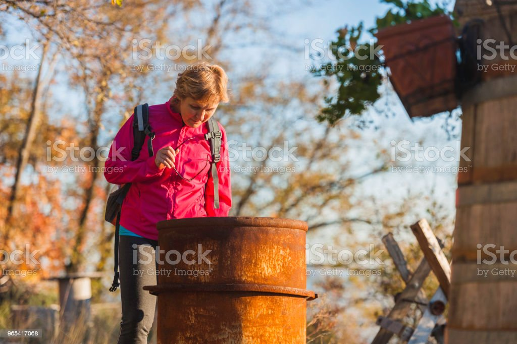 Mature woman watching an old barrel,,autumn colors, Italy,Europe royalty-free stock photo