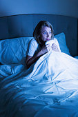 Mature woman watching a scary movie in bed. She is staring at the TV with a frightened expression on her face, under the sheets, clutching her comforter.