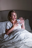 Mature woman watching a scary movie in bed. She is staring at the TV with a frightened expression on her face, under the sheets, hand on her chest.