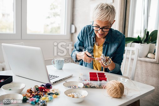 Mature woman watching online tutorials for making jewelry.