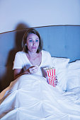 Mature woman watching a movie in bed, eating popcorn. She is staring at the TV with a serious expression on her face, perhaps binge-watching a television show.