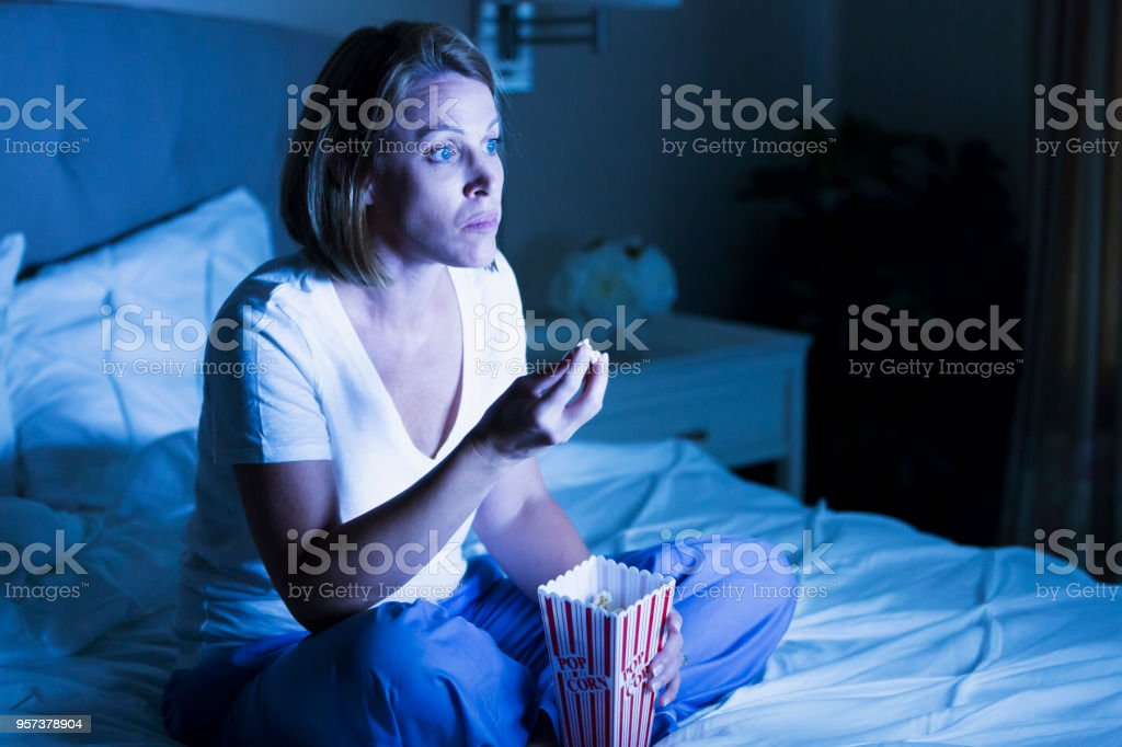 Mature woman watching tv in bed stock photo