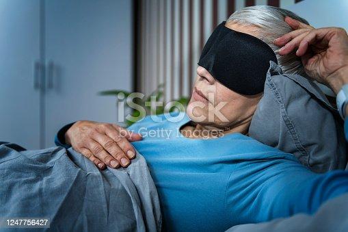 istock Mature Woman Wearing Black Sleep Mask, Lying in Bed 1247756427