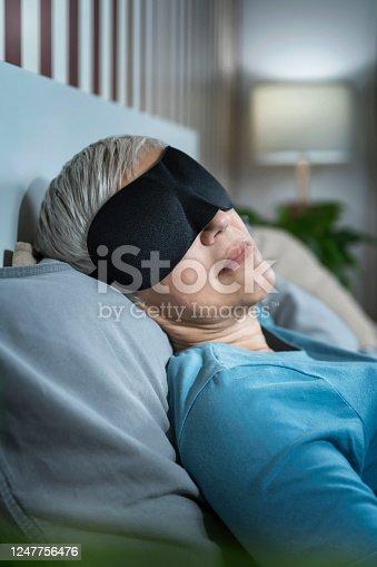 istock Mature Woman Wearing Black Sleep Mask, Lying in Bed 1247756476