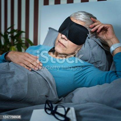 istock Mature Woman Wearing Black Sleep Mask, Lying in Bed 1247756508