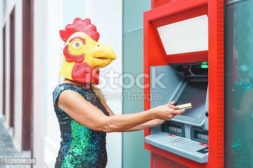 istock Mature woman wearing cock mask withdraw money from bank cash machine with debit card - Surreal image of half human and animal - Absurd and crazy concept of ATM advertise 1125098139