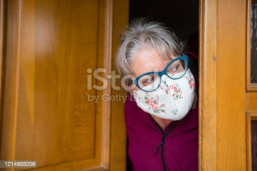 Mature Woman Wearing Homemade Protective Face Mask and Looking Out From Her Home.