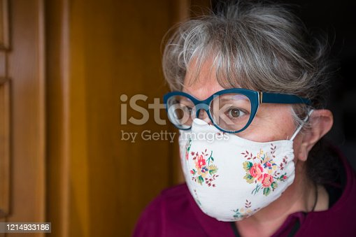 Mature Woman Wearing Homemade Protective Face Mask at Front Door.