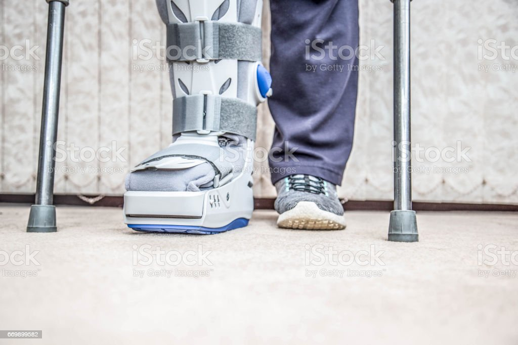 mature woman wearing leg brace and crutches stock photo