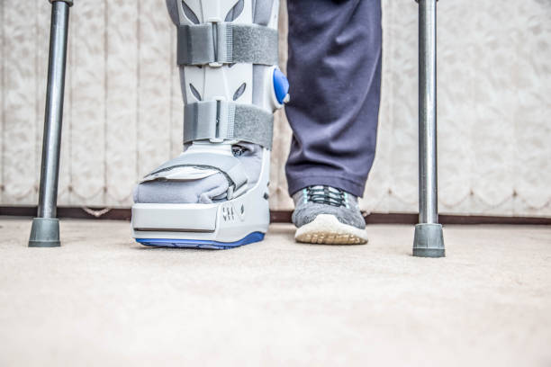 mature woman wearing leg brace and crutches - broken leg stock photos and pictures