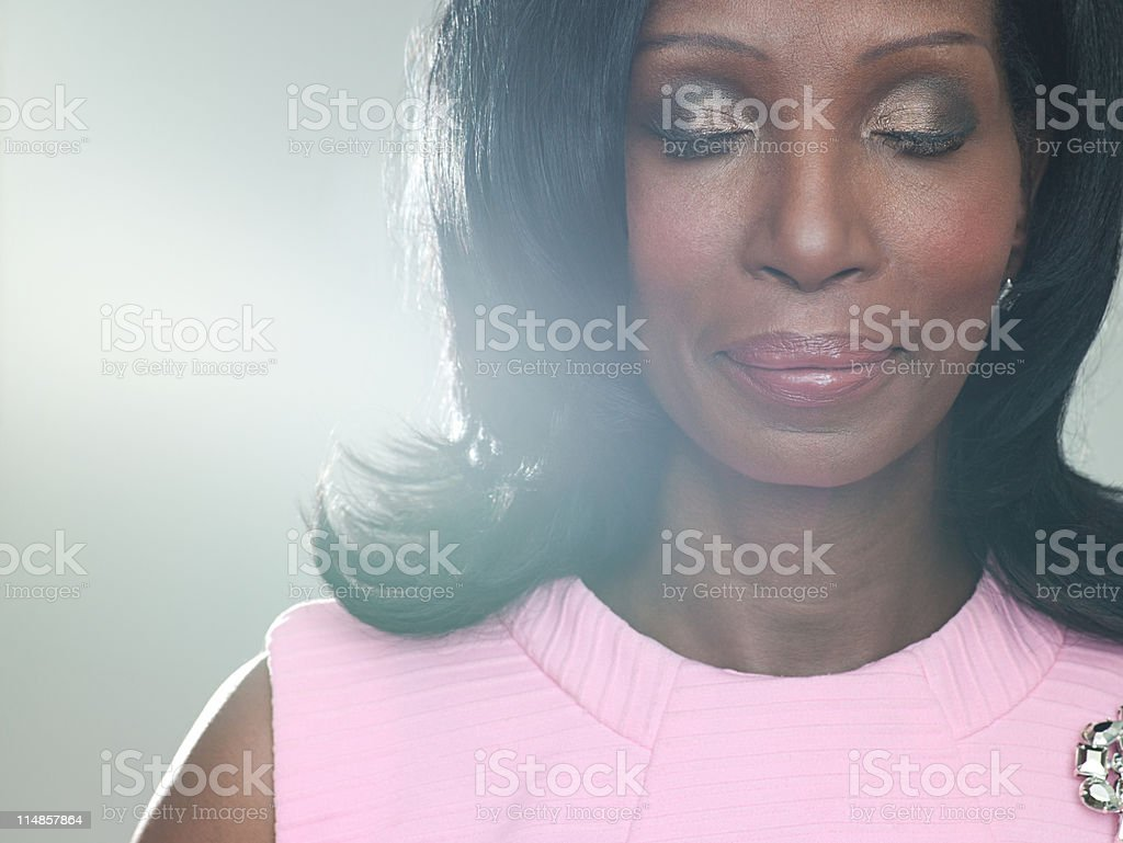 Mature woman wearing pink dress with eyes closed, portrait royalty-free stock photo