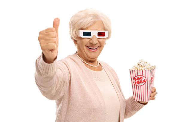 Mature woman with 3D glasses and popcorn making a thumb up gesture stock photo