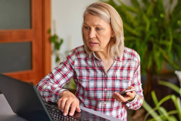 Mujer madura con un teléfono en la mano mirando a la computadora portátil - foto de stock