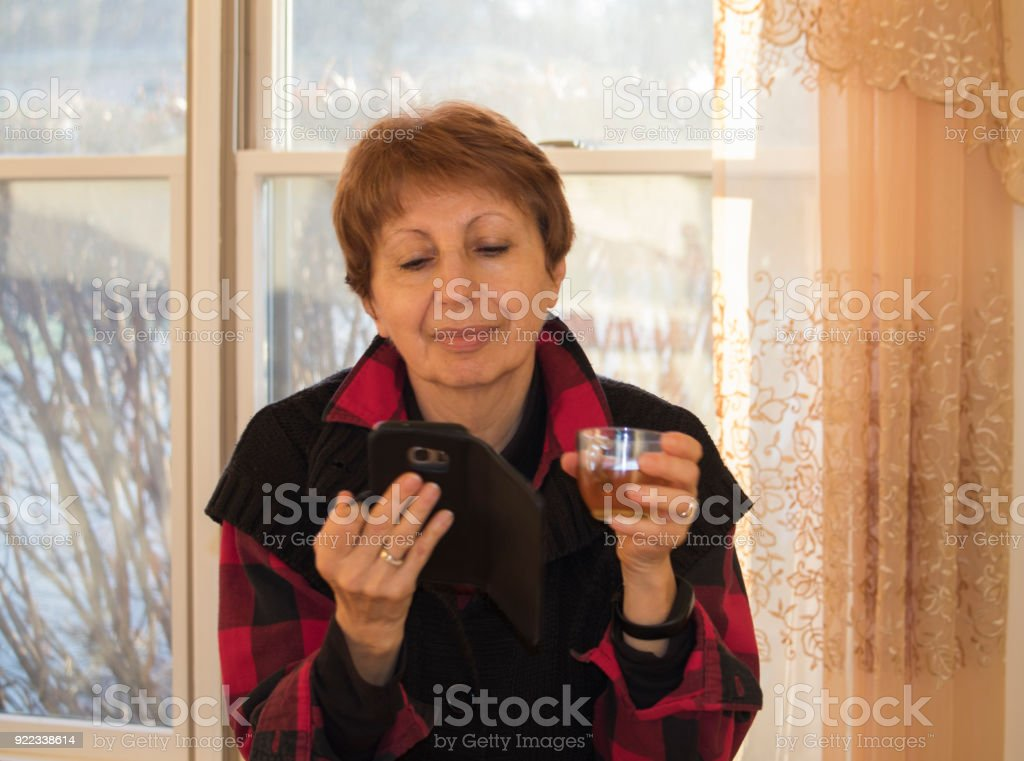 Mature woman with a smart phone stock photo