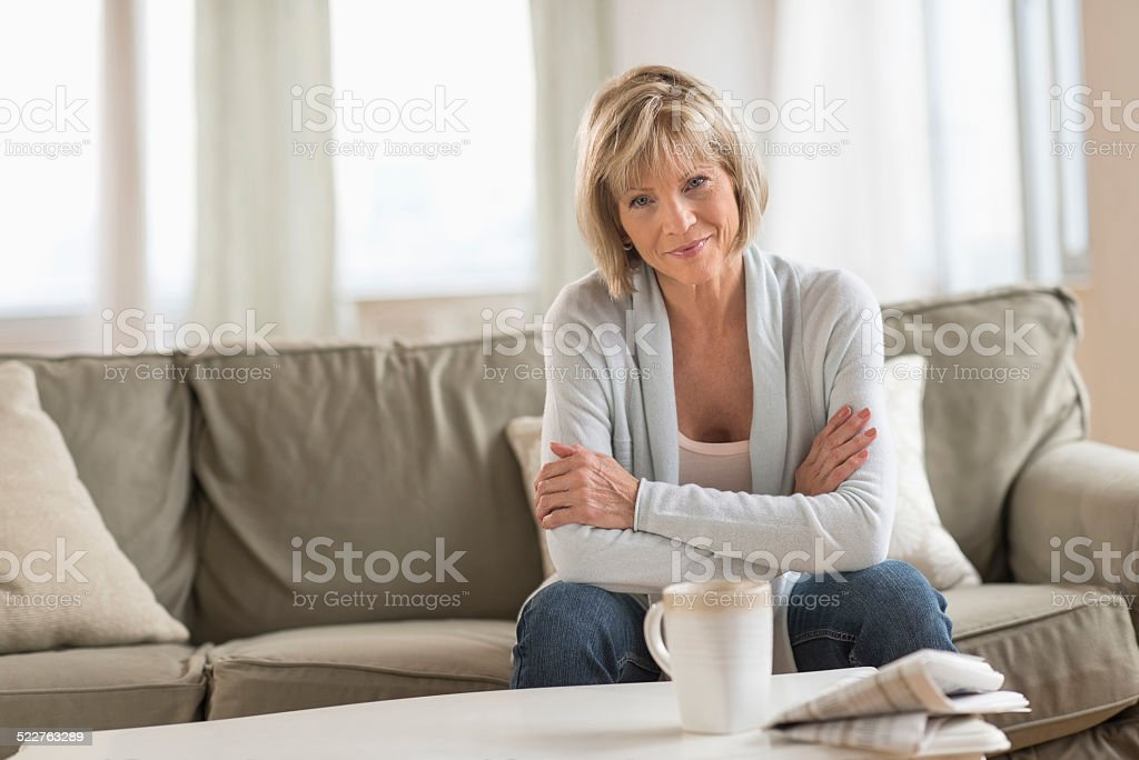 Mature Woman With Arms Crossed Sitting On Sofa stock photo