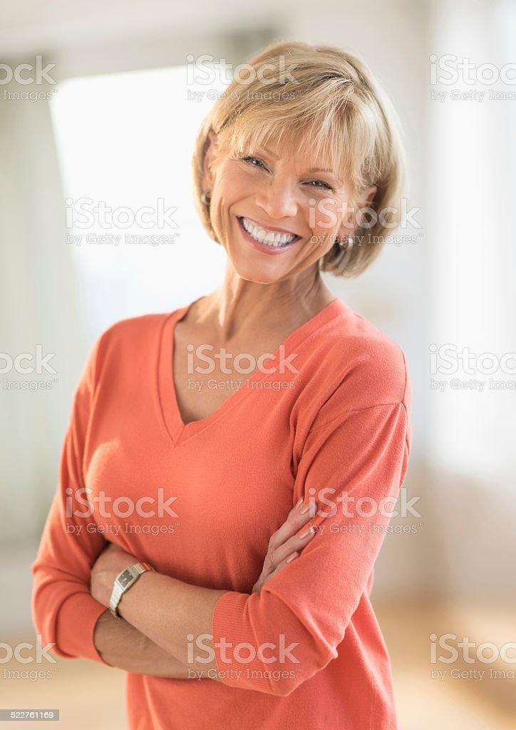 Moden kvinde med krydsede arme Stående der hjemme Stockfoto Flere billeder af 50-59-1534