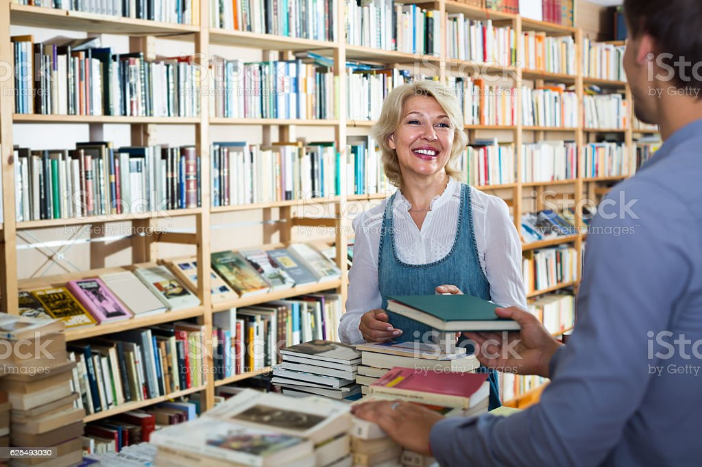 mature woman with assistant in book store stock photo