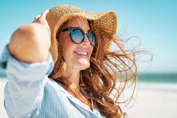 donna matura con cappello da spiaggia e occhiali da sole - protezione foto e immagini stock