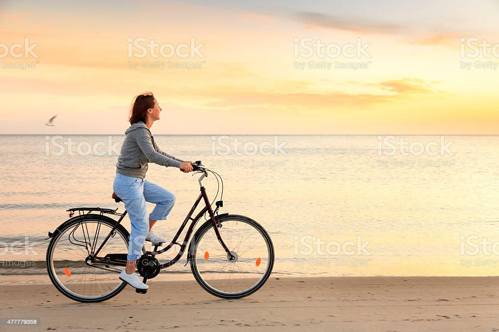 Mature woman with bike on beach at sunset stock photo