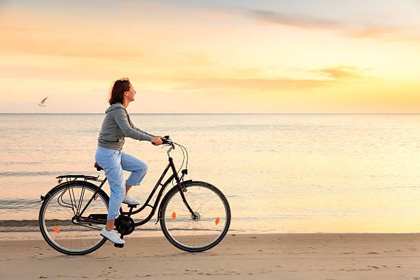 reife frau mit fahrrad am strand bei sonnenuntergang - wellness ostsee stock-fotos und bilder