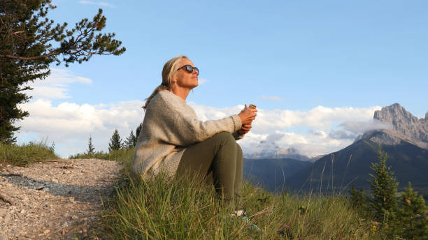 Mature woman with cell phone sits by trail at sunrise stock photo