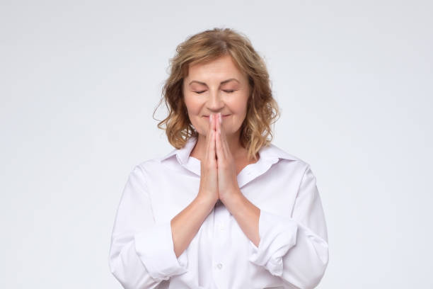 Mature woman with closed eyes with prayer hands pressing together. stock photo