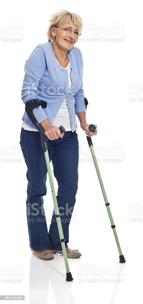 Mature woman with crutches Full lenght portrait of smiling mature woman standing with crutches. Studio shot on white background. 60-64 Years Stock Photo