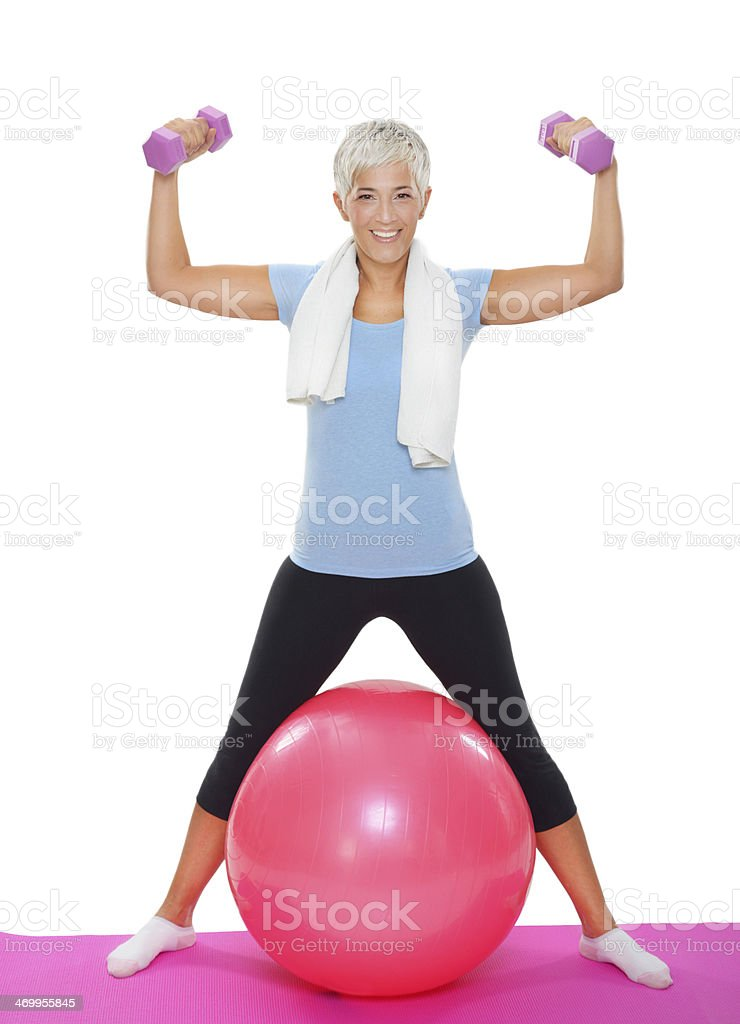 Mature woman with dumbbells on pilates ball royalty-free stock photo