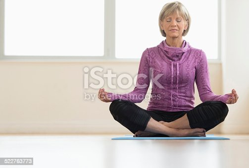 istock Mature Woman With Eyes Closed Sitting In Lotus Position 522763773