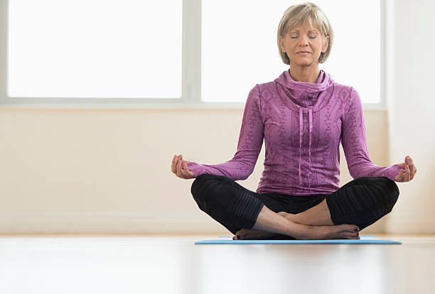Mature Woman With Eyes Closed Sitting In Lotus Position Full length of mature woman with eyes closed sitting in lotus position at home lotus position stock pictures, royalty-free photos & images