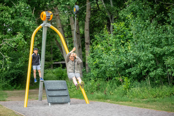 Mature woman with glasses riding a zip-line at an outdoor playground at a public park. stock photo