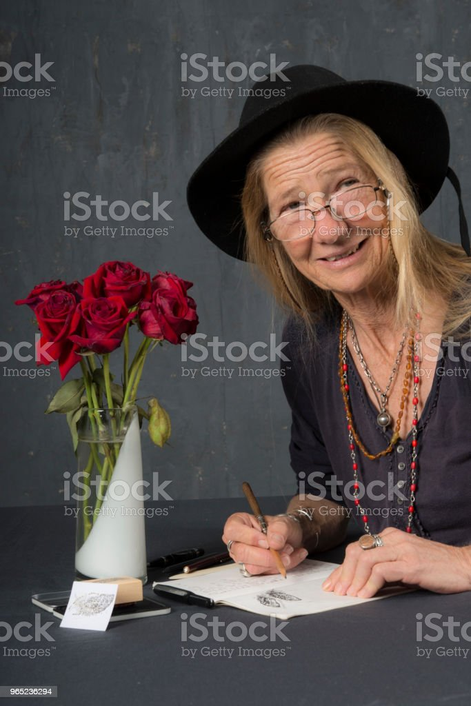 Mature woman with glasses writes at her desk. She looks up and smiles at the camera. zbiór zdjęć royalty-free
