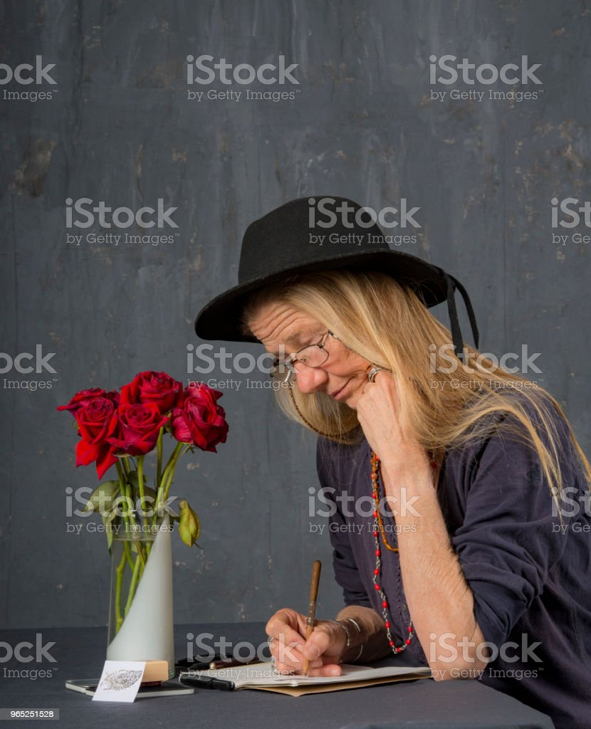 Mature woman with glasses writes at her desk.She concentrates on her task. royalty-free stock photo
