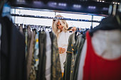 Mature woman with gray hair choosing clothes in clothes shop