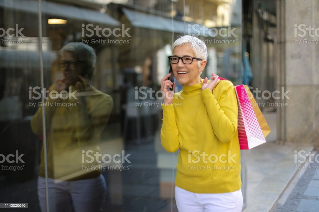 mature woman with a gray hair walking around the city and carrying...