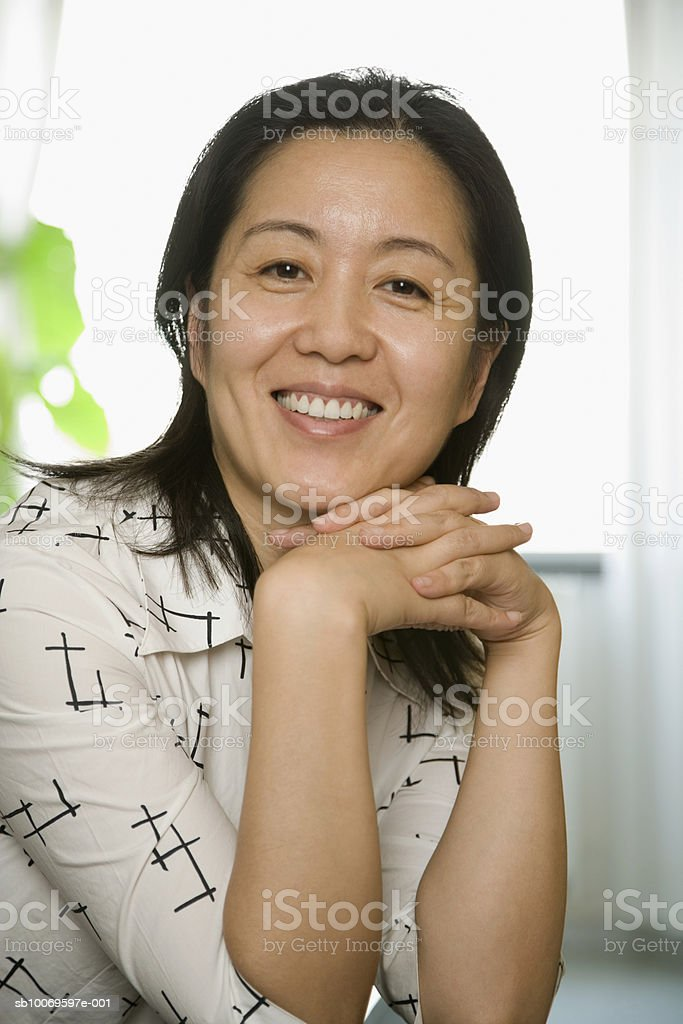 Mature woman with hands clasped, smiling, portrait royalty-free stock photo