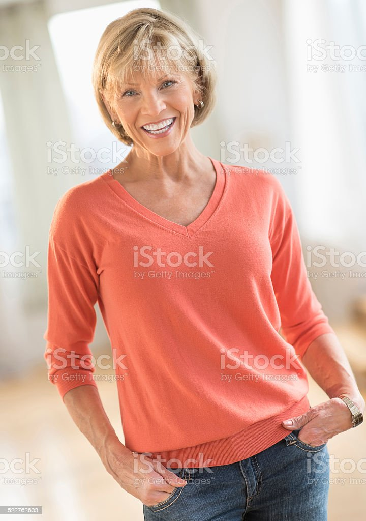 Mature Woman With Hands In Pockets Standing At Home stock photo