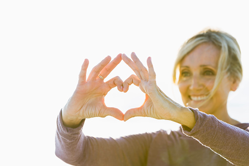 A mature woman in her 50s standing outdoors in the bright sunlight, holding her hands up in the shape of a heart to symbolize love and happiness. She is smiling. The focus Is on her hands.