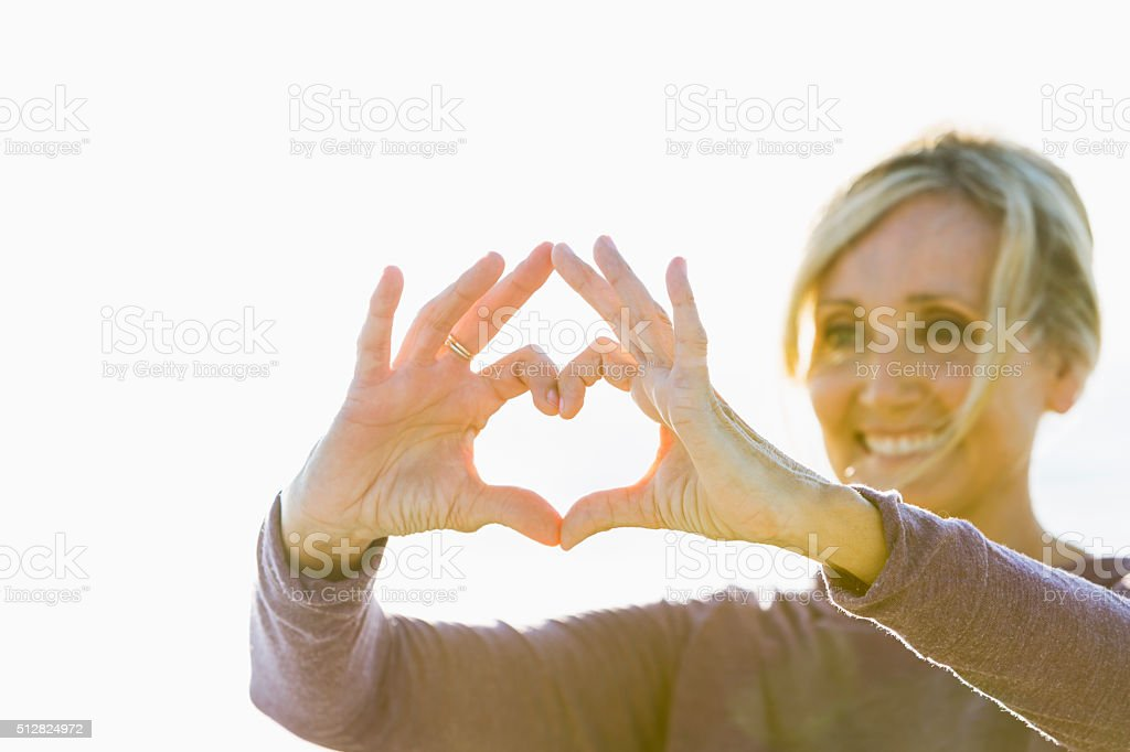Mature woman with hands in shape of heart stock photo