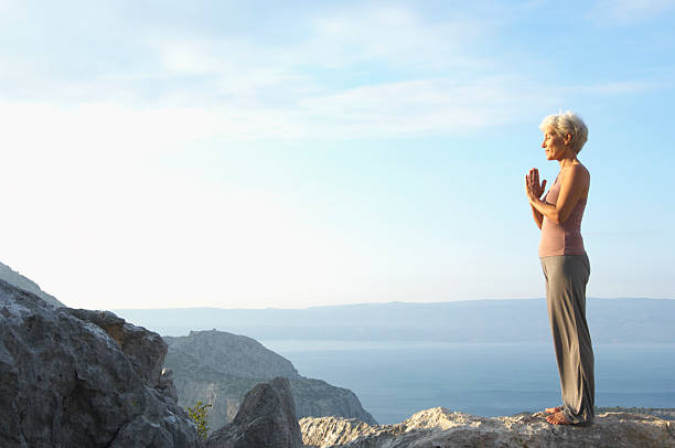 Mature woman with hands pressed together in mountain landscape stock photo