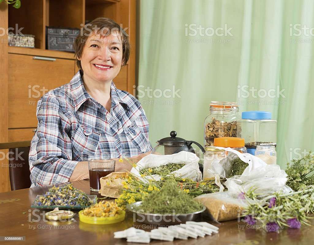 Mature woman with herbs at table stock photo