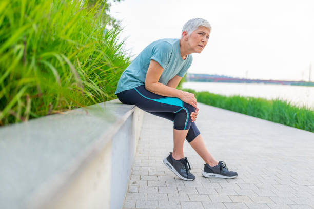 Mature woman with injured knee or leg outdoors. Fitness, sport, exercising and healthy lifestyle concept - Mature woman with injured knee or leg outdoors. Knee injury for senior woman athlete runner. arthritis stock pictures, royalty-free photos & images