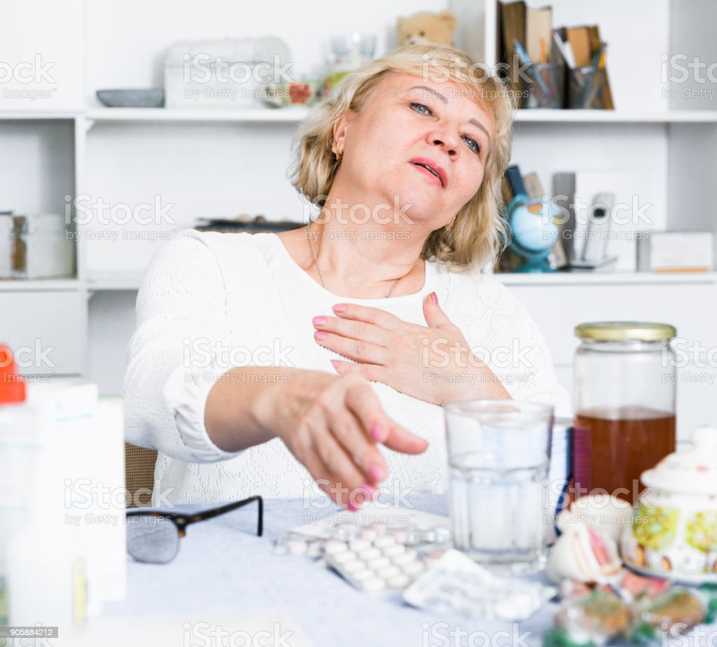 Mature woman with medicines and bills stock photo
