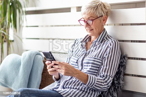 Mature woman with mobile phone on her hands sitting in room and sending messages to her friends and family