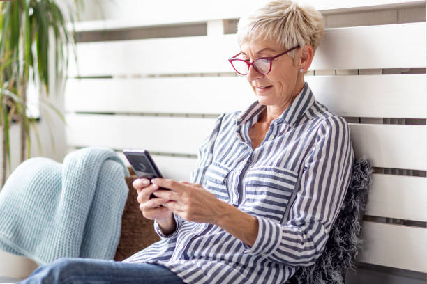 mature woman with mobile phone on her hands sitting in room and sending messages to her friends and family - casa reforma imagens e fotografias de stock