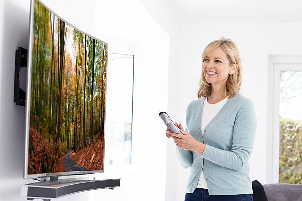 Mature Woman With New Curved Screen Television At Home Mature Woman With New Curved Screen Television At Home 4k resolution stock pictures, royalty-free photos & images