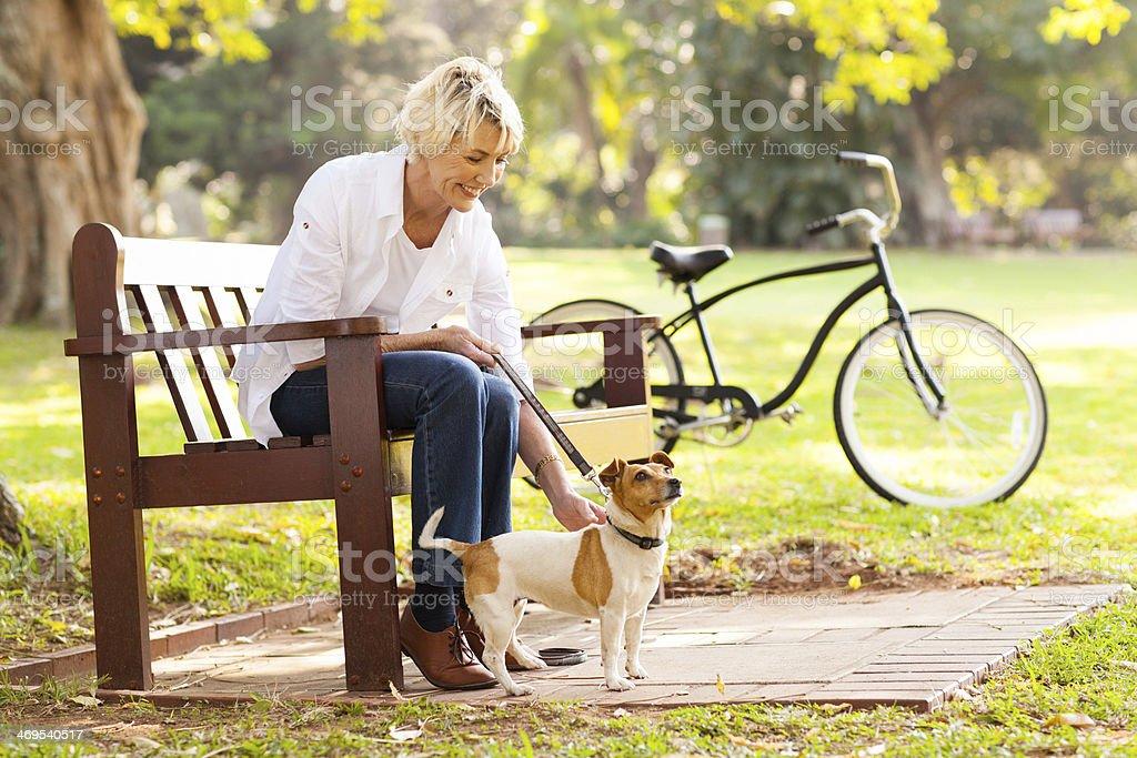 mature woman with pet dog outdoors stock photo