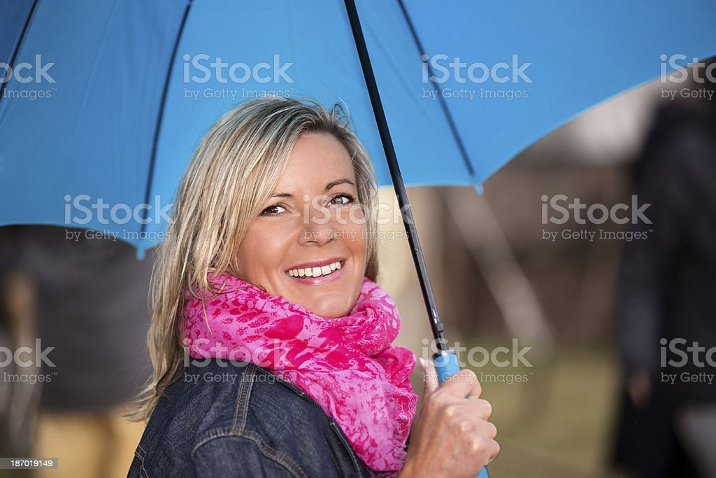 Mature woman with pink scarf and blue umbrella outdoor portrait royalty-free stock photo
