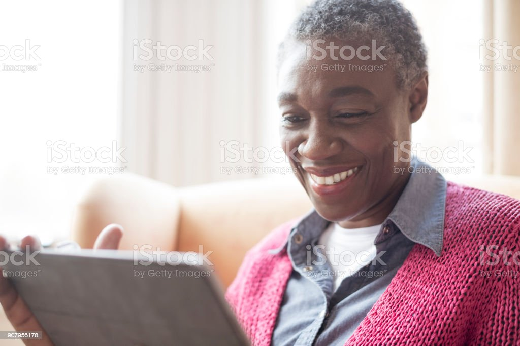 Mature woman with short grey hair surfing the internet stock photo
